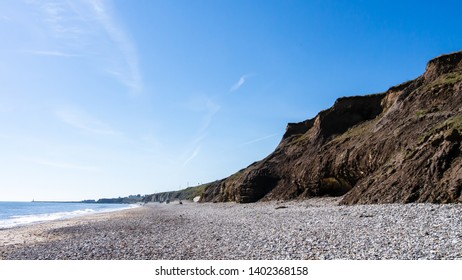 Panorama of cliff faces made of rock and earth at Seaham Hall Beach in County Durham showing blue sky, pebbled beach and a calm North Sea.