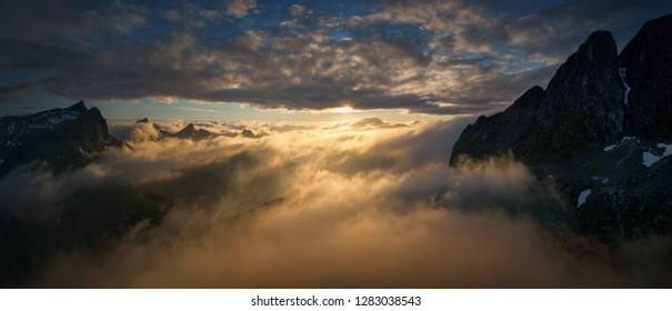 Panorama of the cloudy mountains around Mefjorden in sunset light, Senja