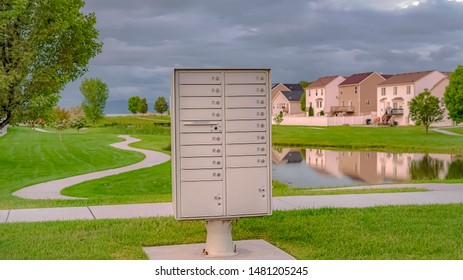 Panorama Cluster mailbox against pond and houses under sky with thick gray clouds. Lush trees and a curvy pathway can be seen on the vivid grassy terrain.