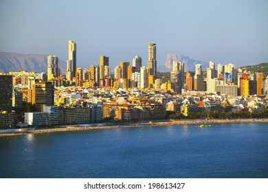 Panorama coast with people relaxing on urban background of houses and hotels (View of the Benidorm, Spain)