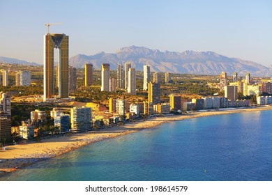 Panorama of the coast with people sunbathing and swimming people on background city hotels and houses (View of the Benidorm before sunset, Spain)