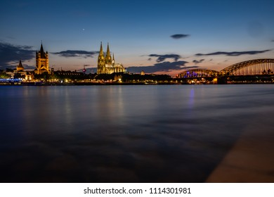 Panorama Cologne Cathedral, Great St. Martin's Church and Hohenzollern Bridge at night during the blue hour on the Rhine.