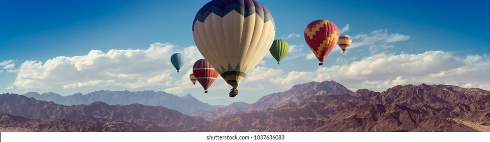Panorama with colored hot air balloons above mountain peaks for your billboard or web header of travel concept.