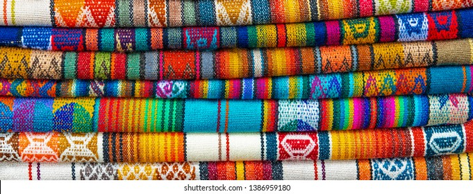 Panorama of colorful Andes textiles on the local art and craft market of Otavalo, Ecuador. Peru and Bolivia boast the same style of indigenous fabrics.