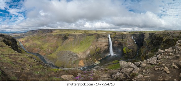 Panorama of colorful gorge with four waterfalls Haifoss, the fourth highest waterfall(122m) of the island, and Granni. The viewpoint on the sheer cliffs at the edge of canyon.