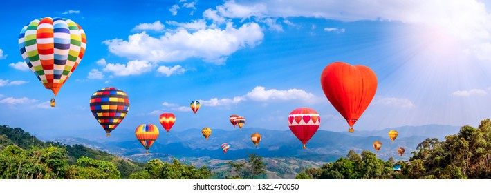 Panorama of colorful hot air balloon fly over mountain view with sunlight,  blue sky and white cloud at  Chiangrai, Thailand