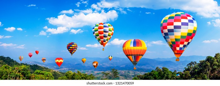 Panorama of colorful hot air balloon fly over mountain view with blue sky and white cloud at  Chiangrai, Thailand