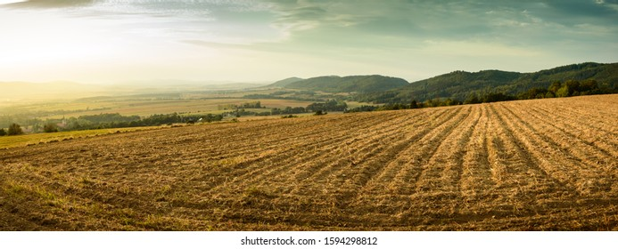 Panorama of colorful mountains and fields landscape illuminated by sunset.