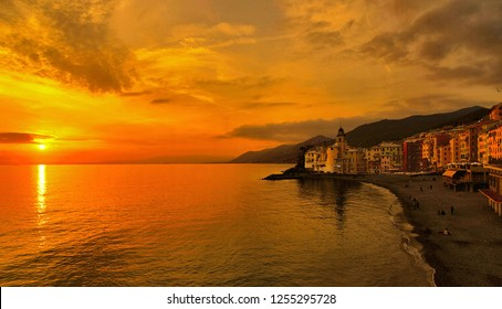 panorama with colorful warm orange sunset and old buildings and church in camogli village and beach in liguria, nothern italy