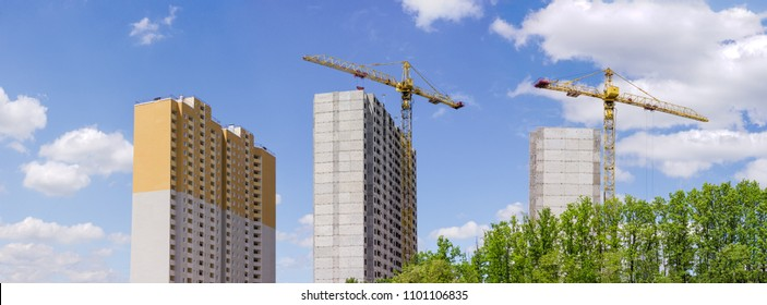 Panorama of the construction of the multi story residential houses from precast concrete panels with building tower cranes and trees in the foreground against of the sky
