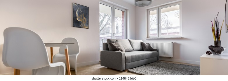 Panorama of contemporary apartment with beautiful white chairs, table and sofa