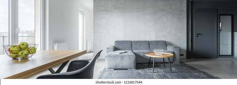 Panorama of contemporary apartment with wooden table and couch