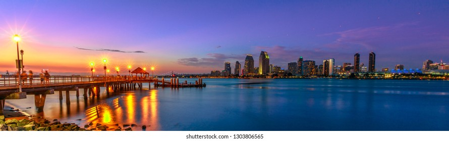 Panorama of Coronado old pier reflecting on in San Diego Bay from Coronado Island, California, USA. San Diego cityscape skyline with Downtown and Waterfront Marina District at twilight on background.