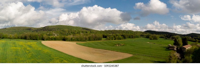 a panorama of the countryside with forests and a cultivated field