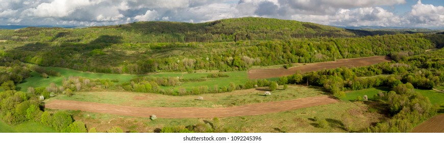 a panorama of the countryside with forests and cultivated fields