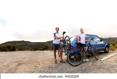 Panorama of a couple who have finished mountain biking outdoors and are loading the bicycles onto the car bike rack. large image, lots of copyspace, healthy lifestyle scene.