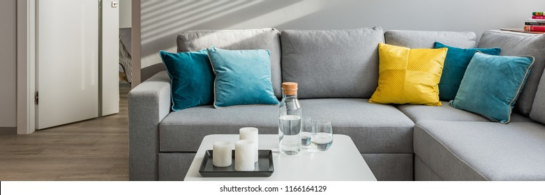 Panorama of cozy living room with corner sofa, colorful cushions and white coffee table