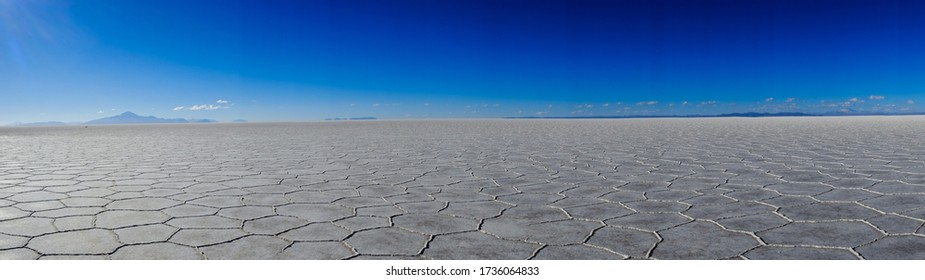 Panorama of the cracked surface of the Salar de Uyuni with mountains in the background in the Andes of Bolivia