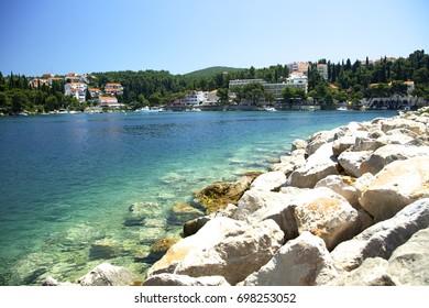 Panorama of Croatian coast. Azure sea and stones, small town