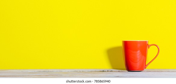 Panorama cropped shot of bold colored red coffee mug on wood desk with yellow background and shadow