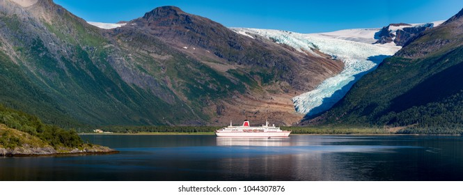 Panorama of cruise ship at Svartisen glacier in Norway, Scandinavia, Europe. Travel by water. Mountain in background.