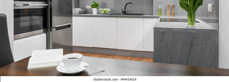 Panorama of cup of coffee on wooden dining table standing in white, modern kitchen