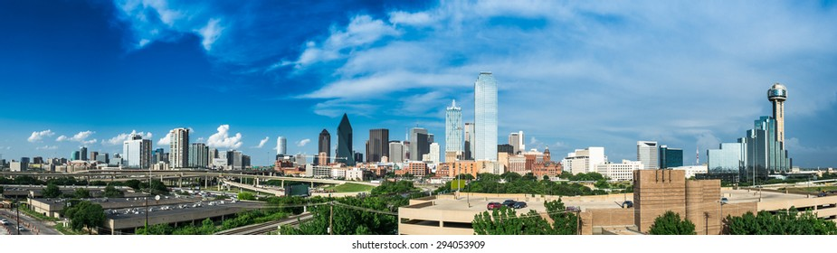 Panorama of the Dallas Texas Skyline on a partly cloudy day. Summertime foliage in the foreground