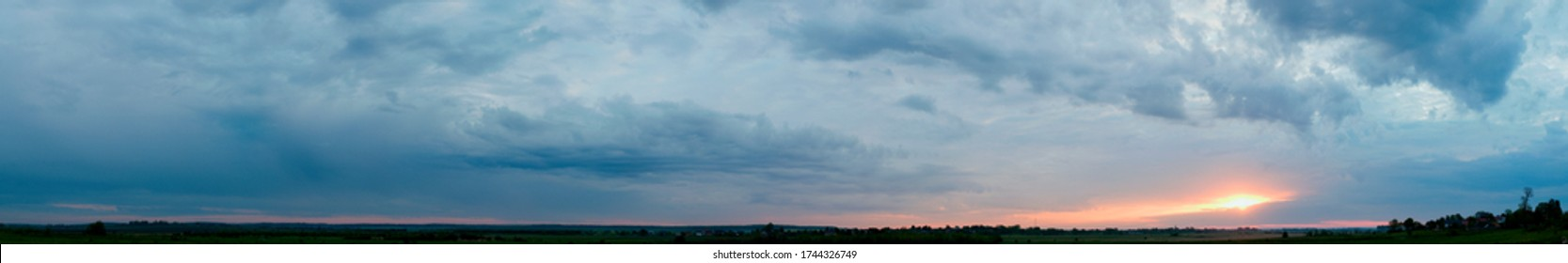 Panorama of dawn fire in the sky above the natural pasture. Golden red clouds just before sunrise. Picturesque landscape at sunrise. Beauty in nature