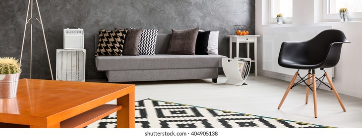 Panorama of a designer living room with wooden coffee table in the foreground