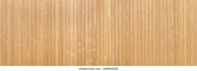Panorama - Detail of a light brown wooden wall made of vertical tongue and groove boards