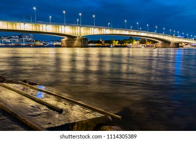 Panorama with the Deutzer bridge and the Severins bridge in the background at night during the blue hour, in the foreground a pier for boats.