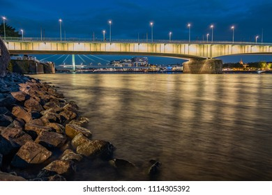Panorama with the Deutzer Bridge and the Severins Brücke in the background at night during the blue hour, in the foreground old rock formations.