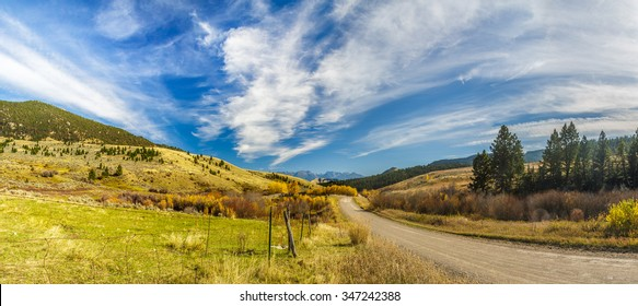Panorama of a dirt road in the colorful autumn countryside of Montana