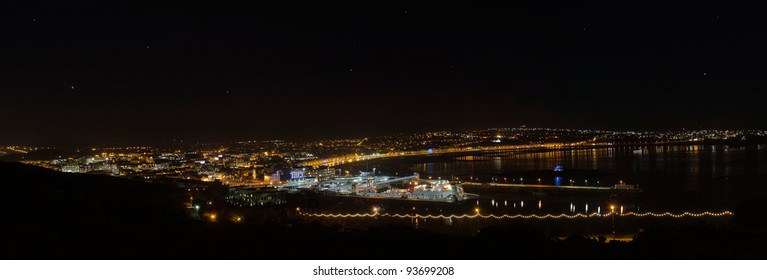 Panorama of Douglas Bay on Isle of Man with Boat in the harbour and a night sky.