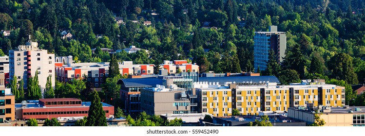 Panorama of downtown residential and commercial district of Eugene, Oregon set in the midst of lush green trees.
