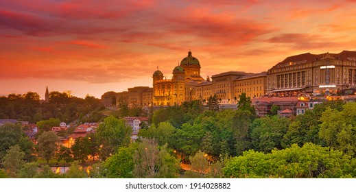 Panorama dramatic red sunset sky and Federal Palace in Bern, Switzerland. Swiss Parliament building skyline. Landmark of historical old town Bern, Capital of Switzerland, UNESCO World Heritage Site.