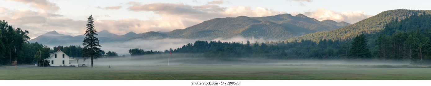 Panorama of early morning mist in the Adirondacks National Park. White house in a field with big tree and mountains in the background. Shot in the countryside of Keene (Lake Placid), NY, USA.