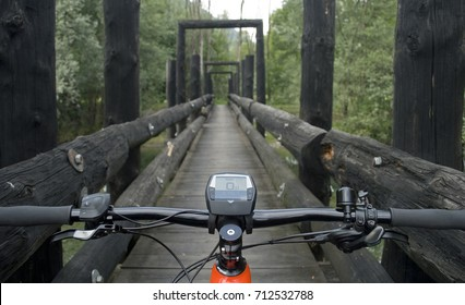 Panorama: Ebike E-bike electric bicycle orange, detail of handlebar, leaning on an old dark wooden bridge, in the woods, beneath which flows a small light green mountain river, Ossola, Alps, Italy