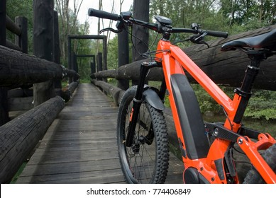 Panorama: Ebike E-bike electric bicycle orange, detail from back, leaning on an old dark wooden bridge, in the woods, beneath which flows a small light green mountain river, Ossola, Alps, Italy