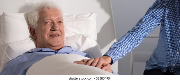 Panorama of elder patient holding hands with his grandson