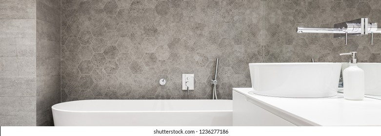 Panorama of elegant bathroom with white bathtub and oval washbasin