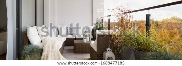 Panorama of elegant decorated balcony with rattan outdoor furniture, bright pillows and plants