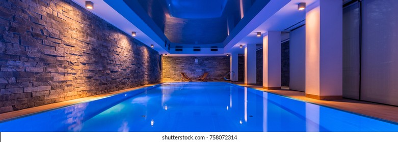 Panorama of elegant swimming pool with decorative led lights and brick wall