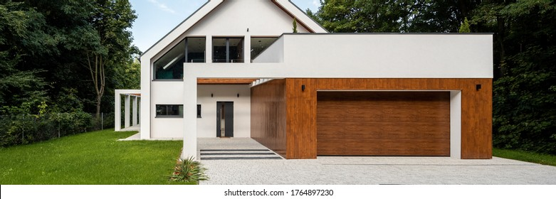 Panorama of elegant white house with wood decor on garage and green lawn