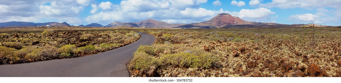 Panorama of empty road crossing the lava in the mountain, Lanzarote, Canary islands, Spain. Vertical view