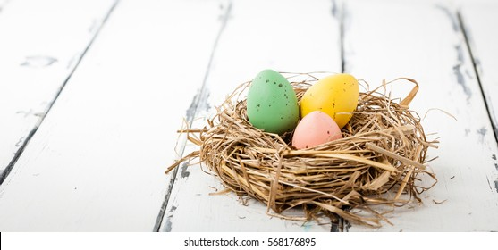 panorama of Ester eggs in a a bird nest on white wooden background