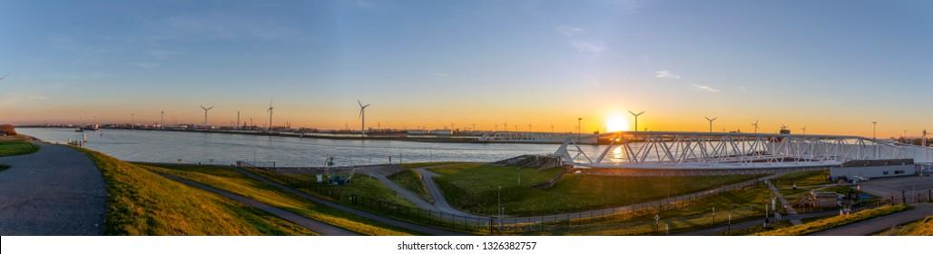 Panorama Europoortkering or Maeslandkering part of the Deltawerken in the Nieuwe Waterweg at sunset with many wind mills.