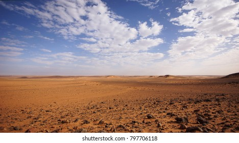 Panorama of the eye of Africa in eastern Mauritania, orange stone and sand desert under a blue sky with some white clouds