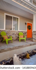Panorama Facade of home with bright orange front door decorated with a festive wreath