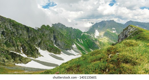 panorama of fagaras mountain ridge in summer. spots of snow on grass of steep slope. rocky tops. cloudy weather. romania landscape